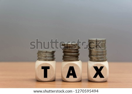 Wood cube tax word and coin money stack on wooden table background.  Tax Day 2019 takes place on April 15 copy space.
