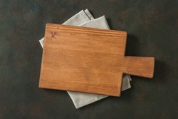 Wood cutting board over towel on stone kitchen table. Top view. Food background Cutting board wood table