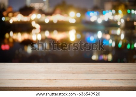 Wood desk empty for present product and blur bokeh night city. #636549920