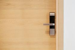 Wood door with digital door lock systems best security protection for apartment. Electronic door handle installed on wood door. Selective focus
