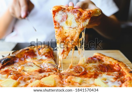 Wood fire cheesy pizza slice in hand. Traditional Hawaiian and Salami pizza savory dish flavour of origin Italian restaurant. Wood-Fired Oven Pizza with people holding and cutting knife background Stock photo ©