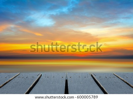 Wood floor scene of beautiful sunset sunrise sky over sea beach. Summer holiday relax background with copy space for decorate design.