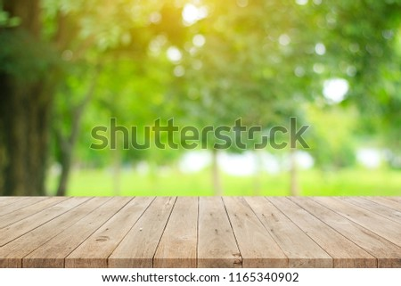 Wood floor with blurred trees of nature park background and summer season, product display montage #1165340902