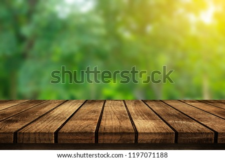 Wood floor with blurred trees of nature park background and summer season, product display montage #1197071188