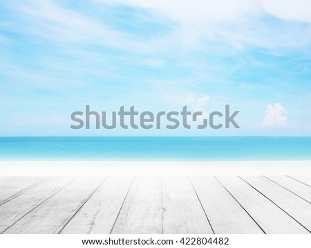 Wood floor with white blue surfing wave background. Blue water and sky bright. Nature wallpaper blur of sea daytime. Focus to wooden in the foreground. Timber pattern texture stage.