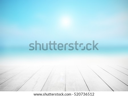 Wood floor with white surfing wave background. Blue cool water and sky bright rays light. Nature wallpaper blur of sea daytime. Focus to wooden in the foreground. Timber pattern texture stage.
