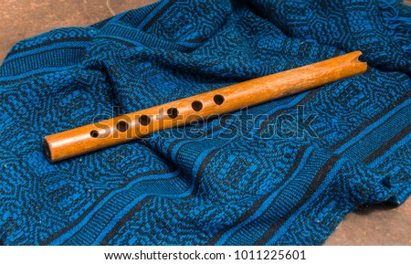 wood flute called quena, traditional Andean instrument in a still life #1011225601