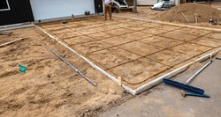 Wood frame and reinforcing steel rods, or rebar, used in preparation for concrete driveway at a construction job site.