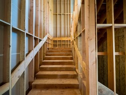Wood frame staircase under construction inside a building with unfinished wall