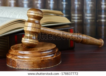 Wood gavel, soundblock and open book on the background of shelves of old books