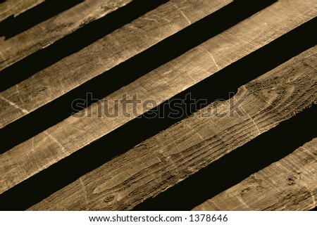Wood grain and dark shadows on panel fencing.