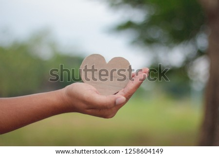 Wood heart in hand on green background.Love valentine concept. #1258604149