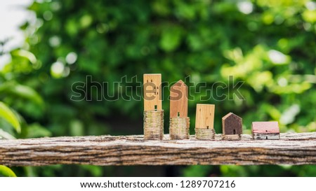 Wood house model and row of coin money on wood table with blur green leaves nature background, Real Estate market, Trading Estate, Mortgage Concepts
