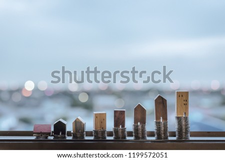 Wood house model and row of coin money on wood table with light blue background, Real Estate market, Trading Estate, Mortgage Concepts