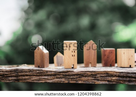 Wood house model on wood and blur green leaves background, a symbol for construction , ecology, loan, mortgage, property or home.