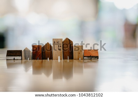 Wood house model on wood table , a symbol for construction , ecology, loan, mortgage, property or home.