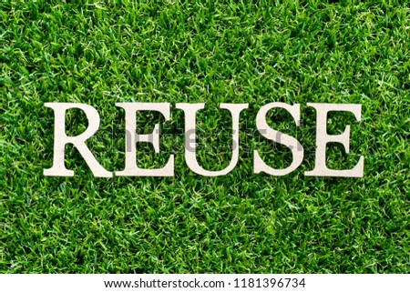 Wood letter in word reuse on artificial green grass background