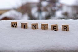Wood letters, word winter on the snow