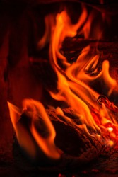 Wood log burning in the chimenea. Fire wood, coal and amber ash closeup. Red tongues of flame and glowing amber.