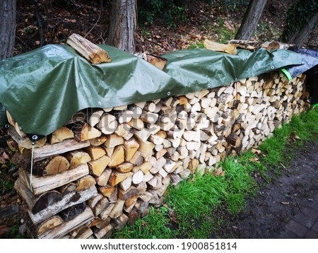 Wood logs for fireplace stacked outside and covered with a tarpaulin Сток-фото ©