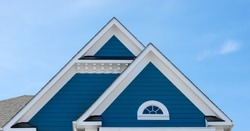 wood looking vinyl white trim roof decoration gable, corbel, louver with pacific blue horizontal siding on a luxury American single family home in the East Coast USA with blue sky background
