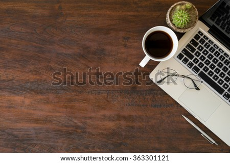 Wood office desk table with laptop, a cup of coffee and eye glasses. Top view with copy space. Warm vintage tone.