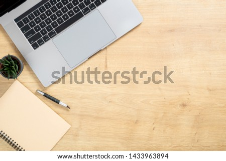 Wood office desk table with laptop computer, succulent plant, paper notepad, pen. Minimal flat lay style composition with copy space, top view, overhead. Business woman workspace concept.  #1433963894