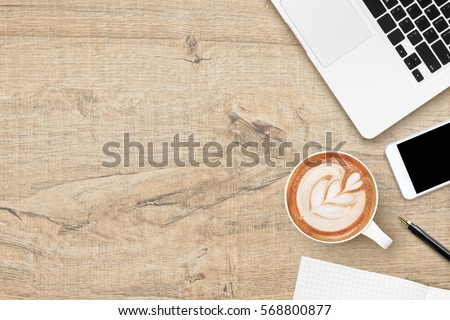 Wood office desk table with laptop, smartphone, coffee cup and supplies. Top view with copy space, flat lay.
