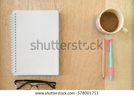 Wood office table with glasses, cup of coffee, notebook and supplies.Top view with copy space, flat lay. Business table concept.