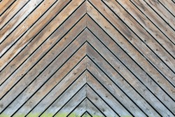 Wood panel as background. Old vintage diagonal planked wooden texture. The planks are put together by herringbone pattern.
