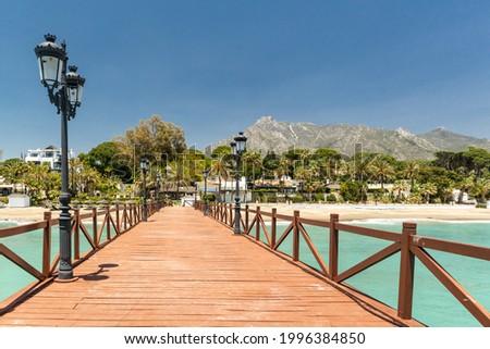 Wood path in Marbella. Red wood bridge in Puente Romano, luxury area of Marbella city. In background famous La Concha mountain. Emerald water colour.  Foto stock ©