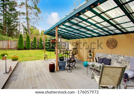 Wood patio pergola with iron table set, sofa and chairs overlooking beautiful green lawn and fir trees. Patio area decorated with iron arts and flower pots.