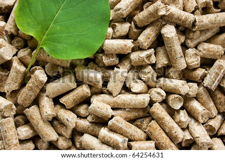 Wood pellets with a green leaf - stock photo