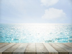 Wood perspective at coast on sea blur image. wood table top on blurred blue ocean. travel summer holidays concept.