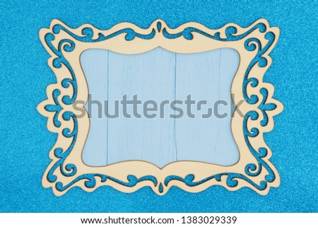 Wood picture frame on a blue glitter background with copy space for your message