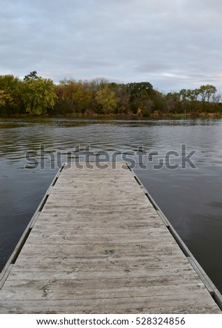 Wood pier along a river on a fall morning #528324856