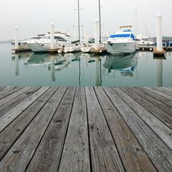Wood platform beside yachts at marina.