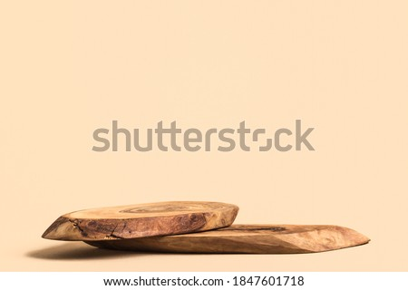 Wood podium on beige background for cosmetic product mockup.