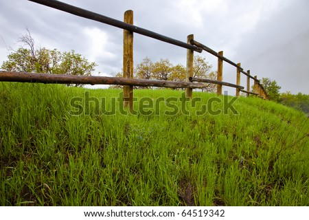Wood pole fence on a grassy hill