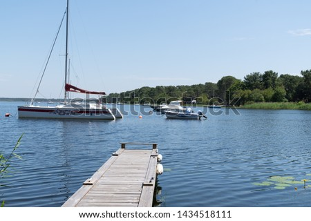 wood pontoon in lake in Lacanau city in France with sail boat in summer water