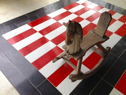 Wood rocking horse on red,white and black tile