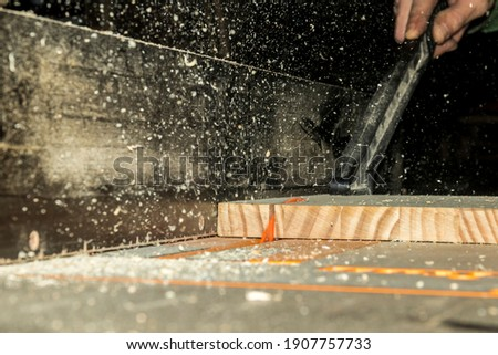 wood saw machine cutting plank and flying chips 商業照片 ©