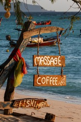 Wood sign of coffee, massage, fishing text at beautiful Thailand travel island
