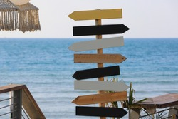 Wood signs on the beach. Direction signpost on sea background.