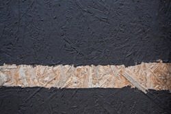 Wood splinter wall texture painted black with one stripe left in natural wood color, copy space
