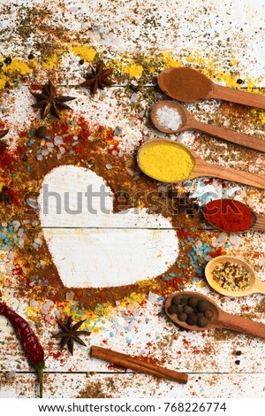Wood spoons with turmeric, paprika, sea salt, cinnamon, anise and scattered seasoning. Set of spices on white wood background. Composition of condiment making heart shape. Cuisine and flavours concept #768226774