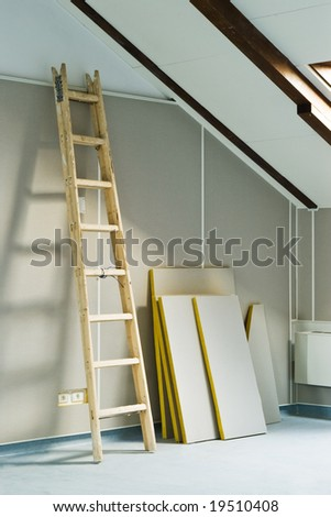wood step ladder and construction materials in attic room