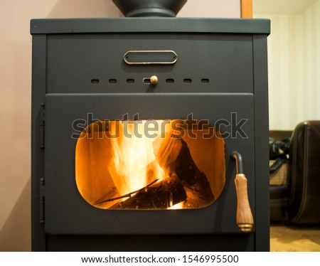 Wood stove and wood burning inside. Fire in heating stove. #1546995500