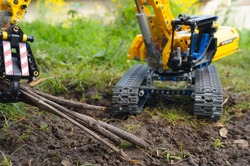 Wood strands representing tree branches are lifted from a muddy soil by the hydraulic grapple of a scale model (a Lego child's toy) of a yellow tracked excavator turning on its chassis, in a garden