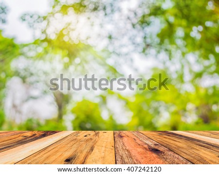 wood table and blur image of Abstract Bokeh of tree green color background. #407242120